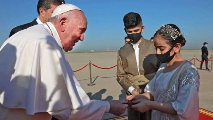 The Pope receives flowers from a woman during his visit to Iraq.