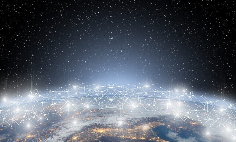 Aerial image of a city at night with a graphic representation of a network above it.