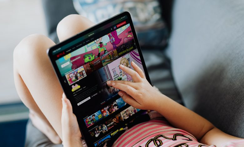 A person accessing Netflix on a tablet