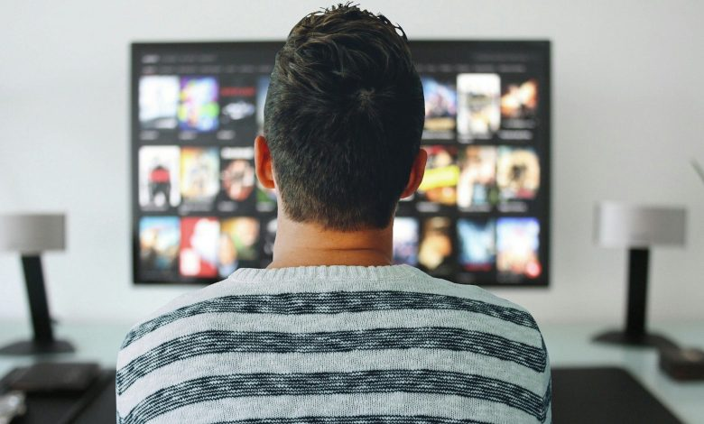 Back view of a man looking at TV screen with video options.