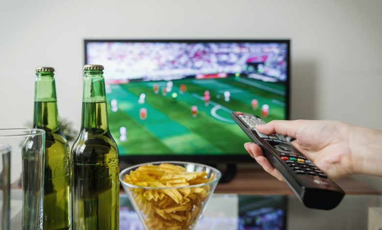 Hand pointing remote control at TV showing football match