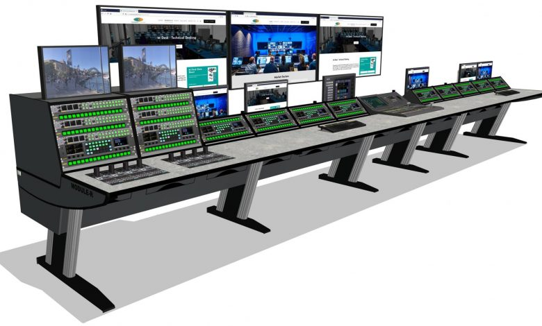 Many monitors and control panels on a very long table